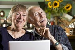 Pares mayores sonrientes con un ordenador portátil Imagen de archivo libre de regalías
