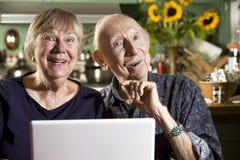 Pares mayores sonrientes con un ordenador portátil Fotografía de archivo