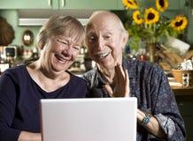 Pares mayores sonrientes con un ordenador portátil Foto de archivo libre de regalías