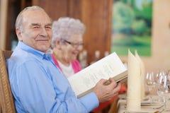 Pares mayores sonrientes en restaurante Imagenes de archivo