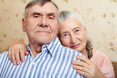 Pares mayores sonrientes felices que abrazan junto en casa imagenes de archivo