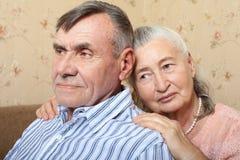 Pares mayores sonrientes felices que abrazan junto en casa foto de archivo