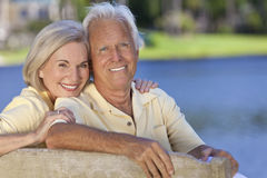 Pares mayores sonrientes felices que se sientan en banco de parque Imagenes de archivo