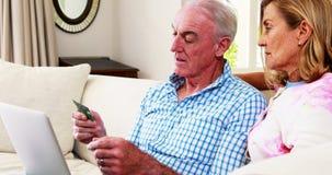 Pares mayores sonrientes que hacen compras en línea en el ordenador portátil en sala de estar almacen de video