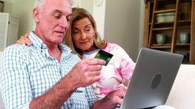 Pares mayores sonrientes que hacen compras en línea en el ordenador portátil en sala de estar