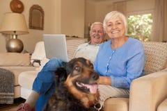 Pares mayores sonrientes que se relajan con su perro en casa Imagen de archivo libre de regalías