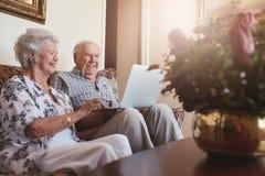 Pares mayores sonrientes usando el ordenador portátil en casa Fotos de archivo libres de regalías