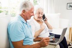 Pares mayores sonrientes usando el ordenador portátil y el smartphone fotografía de archivo libre de regalías