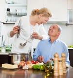 Pares mayores sonrientes y el cocinar junto en cocina Imagen de archivo