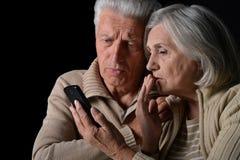 Pares mayores tristes con el teléfono foto de archivo libre de regalías