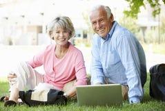 Pares mayores usando el ordenador portátil al aire libre foto de archivo