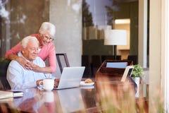 Pares mayores usando el ordenador portátil en el escritorio en casa foto de archivo
