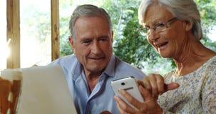 Pares mayores usando el ordenador portátil y discusión sobre el teléfono 4k metrajes