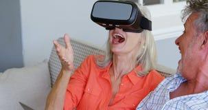 Pares mayores usando el ordenador portátil y las auriculares de la realidad virtual en el sofá 4k almacen de video
