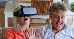 Pares mayores usando el ordenador portátil y las auriculares de la realidad virtual en el sofá 4k almacen de metraje de vídeo