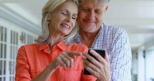 Pares mayores usando el teléfono móvil en el pórtico 4k metrajes