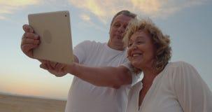 Pares mayores usando la almohadilla táctil al aire libre el vacaciones metrajes