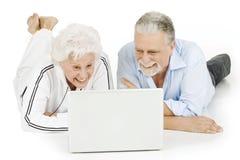 Pares mayores usando la computadora portátil Fotografía de archivo libre de regalías