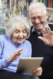 Pares mayores usando la tableta de Digitaces para la llamada video con la familia Imagen de archivo
