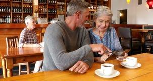 Pares mayores usando la tableta digital en el restaurante 4k metrajes