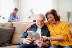 Pares mayores usando la tableta en club del centro de la comunidad foto de archivo libre de regalías