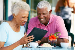 Pares mayores usando la tablilla en el café al aire libre imagenes de archivo