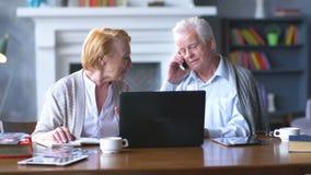 Pares mayores websurfing en Internet con el ordenador portátil Hombre y mujer mayores felices que usa el ordenador almacen de metraje de vídeo