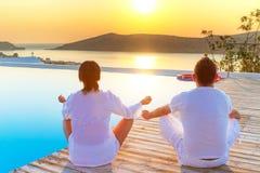 Pares meditating en la salida del sol Foto de archivo libre de regalías