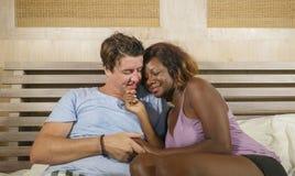 Pares mezclados de la pertenencia ?tnica en el amor que abraza junto en casa en cama con la mujer afroamericana negra juguetona h foto de archivo libre de regalías