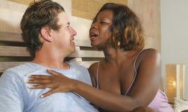 Pares mezclados de la pertenencia ?tnica en el amor que abraza junto en casa en cama con la mujer afroamericana negra juguetona h imagen de archivo