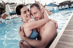 Pares milenares adoráveis que abraçam e que sorriem na piscina fotos de stock