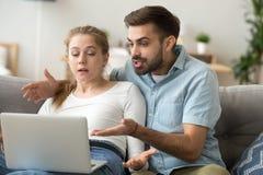 Pares milenares irritados que têm problemas do computador em casa fotografia de stock