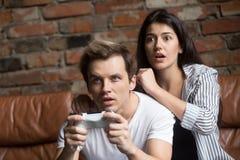 Pares milenares preocupados jogando o jogo de vídeo do computador imagem de stock