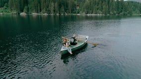 Pares milenarios felices en el barco en el lago alpino almacen de metraje de vídeo