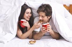 Pares milenarios felices que gozan de las galletas y del café fotografía de archivo libre de regalías