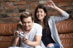 Pares milenarios que juegan a los videojuegos, videojugador joven con emocionado Imágenes de archivo libres de regalías