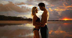 Pares milenarios románticos que se colocan en la playa y que abrazan mientras que las puestas del sol Fotos de archivo