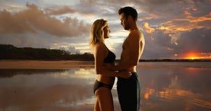 Pares milenarios románticos que se colocan en la playa y que abrazan mientras que las puestas del sol Imagen de archivo libre de regalías
