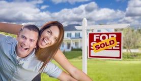 Pares militares novos entusiasmado na frente da casa com sinal vendido Fotografia de Stock Royalty Free
