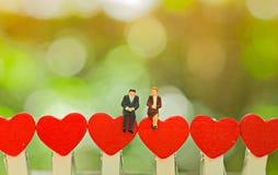 Pares miniatura que se sientan en el corazón rojo, concepto de la tarjeta del día de San Valentín Imagen de archivo