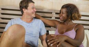 Pares misturados da afilia??o ?tnica no amor que afaga junto em casa na cama com a amiga ou a esposa afro-americana preta brincal fotos de stock royalty free