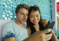 Pares misturados felizes da afiliação étnica no sorriso do amor alegre com o homem caucasiano considerável e a mulher coreana fotos de stock royalty free