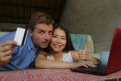 Pares misturados felizes e entusiasmados novos da afiliação étnica com a mulher chinesa asiática e sagacidade de compra caucasian imagem de stock