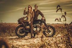 Pares à moda do piloto do café nas motocicletas feitas sob encomenda do vintage em um campo Imagem de Stock