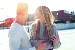 Pares modernos jovenes con la tableta que mira detrás en puesta del sol al aire libre Fotografía de archivo
