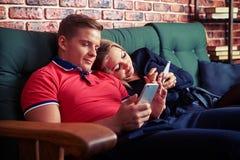 Pares modernos usando el teléfono móvil mientras que se sienta ignorando cada uno más allá del horizonte Fotografía de archivo