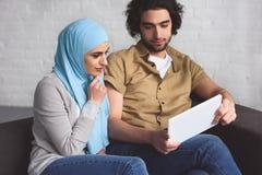 pares muçulmanos usando a tabuleta foto de stock