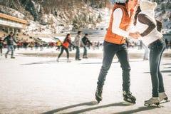 Pares, muchachas felices y patinaje de hielo del muchacho al aire libre en la pista imagenes de archivo