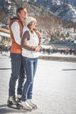 Pares, muchachas y patinaje de hielo del muchacho al aire libre en la pista Imagen de archivo