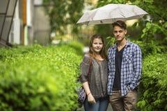 Pares, muchacho joven y muchacha colocándose debajo de un paraguas en la pista verde en el jardín cerca de la casa Foto de archivo